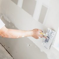 Man spackling new drywall or plasterboard